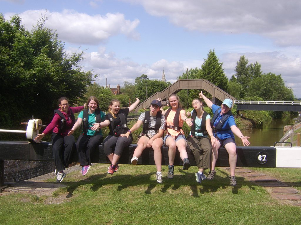 Girls sitting on a beam at a lock